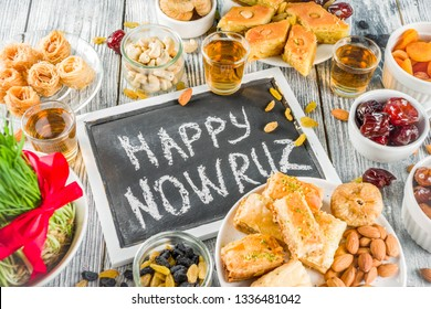 Happy Nowruz holiday background. Celebrating Nowruz sweets and treats- baklava, various dried fruits,  nuts, seeds, wooden background with green grass, copy space top view