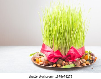 Happy Nowruz holiday background. Celebrating  various dried fruits, nuts, seeds, color  background with green grass wheat, copy space top view