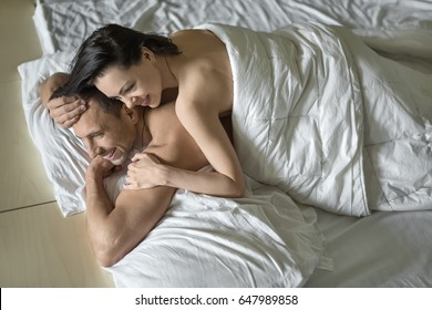 Happy nude couple under the white blanket on the bed. Guy holds his left hand under the chin and right hand on the head. Girl lies on his back. They both smiling. Closeup. Horizontal.