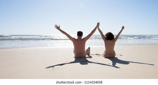 happy nudist couple nude sit on naturism beach in summer holidays