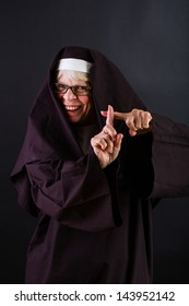 A happy nun crossing her fingers and smiling.