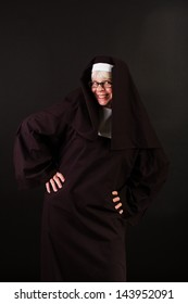 A happy nun with hands on her hips
