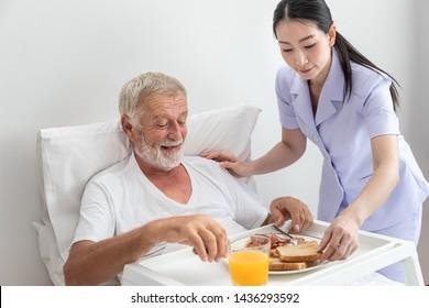 Happy nurse assist and help elderly senior man to eat breakfast on bed in bedroom at nursing home