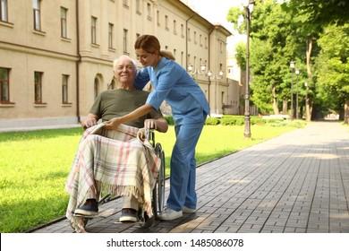 Happy nurse assisting elderly man in wheelchair at park