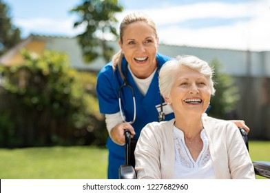 Happy nurse and elderly woman sitting in wheelchair enjoying outdoor. Beautiful nurse with laughing senior woman in wheelchair at outdoor park. Smiling disabled old lady in wheelchair at park.
