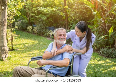 Happy nurse holding elderly man hand on wheelchair in garden at nursing home