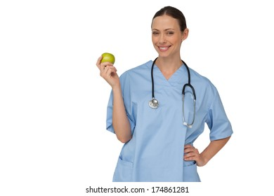 Happy nurse in scrubs holding green apple on white background