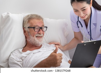 Happy nurse show good health result to elderly man in bedroom at nursing home with thumb up