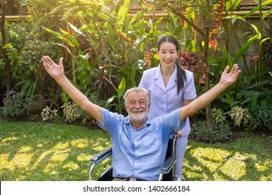 Happy nurse take care elderly man open arms on wheelchair in garden at nursing home looking camera
