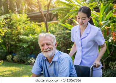 Happy nurse take care elderly man on wheelchair in garden at nursing home looing camera