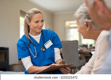 Happy nurse talking to senior patients in private clinic. Senior couple consulting health and medical report with doctor at home. Old man and elderly woman visiting the nurse with clipboard.