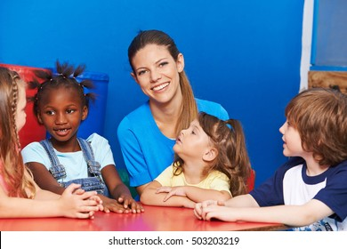 Happy nursery teacher with group of children at a table in kindergarten