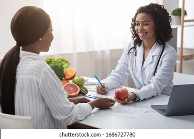 Happy nutritionist black woman giving consultation to patient with healthy fruit and vegetable, nutrition and diet concept