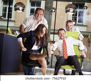 Happy office employees having fun at work in an office chair race.