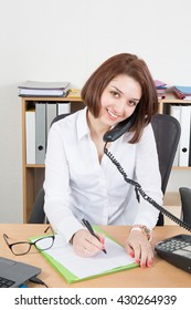 Happy office girl at desk using land line phone, smiling