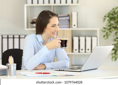 Happy office worker having a coffee break looking away and smiling