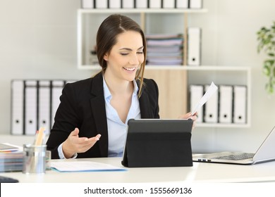 Happy office worker having a video call on tablet at workplace