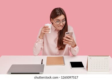 Happy office worker holds cell phone, reads positive news on web page while browses internet, wears trendy spectacles, has laptop computer, tablet, notebook and calendar on desk, poses indoor