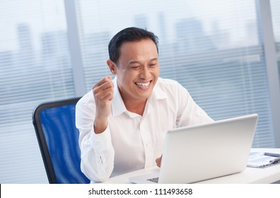 Happy office worker looking with excitement at laptop at office