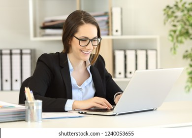 Happy office worker wearing eyeglasses working online writing in a laptop