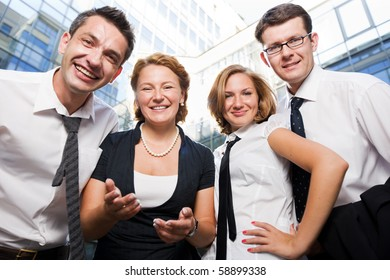 Happy office workers staying in front of office building. Business people office showing team concept outdoors.