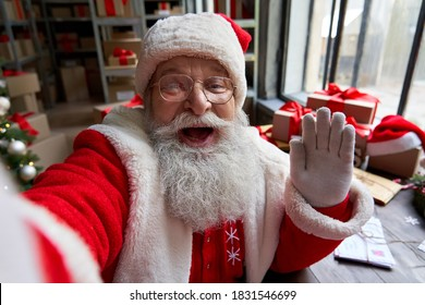 Happy old bearded Santa Claus wearing costume holding phone waving hand taking selfie, video calling, recording video Merry Christmas greeting or shooting vlog standing in workshop, face camera view.