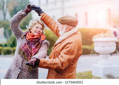Happy old couple dancing at autumn park. Senior ma flirting with blonde elderly woman outdoors in city square in cold weather city street. My love let's dance together. Lifestyle invitation concept.