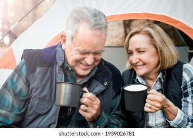 Joyeux vieux couple prenant un café près de la tente dans la forêt