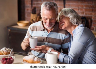Happy old couple having coffee together