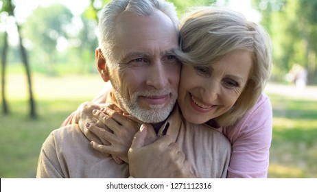 Happy old couple hugging, resting in park together, grandparents closeness