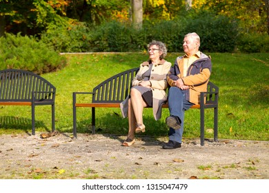 happy old couple in the park sitting on a bench in autumn