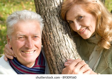 happy old couple posing in the park