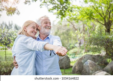 Happy old couple smiling dancing in a park on a sunny day, hoot senior couple relax in the forest spring summer time. Healthcare grandparents lifestyle retirement concept