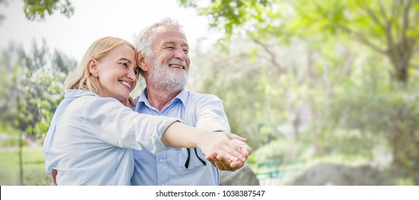 Happy old couple smiling dancing in a park on a sunny day, hoot senior couple relax in the forest spring summer time. Healthcare lifestyle retirement grandparents concept panoramic banner