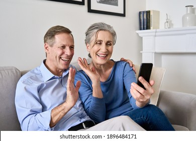 Happy old couple waving hands making online video call on cell phone. Mature retired 50s grandparents enjoying virtual meeting videocall chat, talking, looking at smartphone sitting on couch at home.