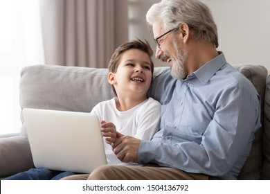 Happy old grandfather and little cute grandson laughing enjoying using laptop together sit on sofa, two age generations grandkid boy having fun with senior grandpa spend time with computer at home