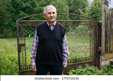 A Happy old grandfather smiling and standing on the background of vegetable garden fence in the yard in the village. The older generation.