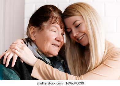 Happy old grandmother hugging  grandchild girl looking at camera, smiling mature mother, headshot portrait