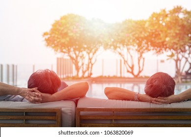 Happy old husband and wife in hospice residence. Relax easy senior retire woman and man couple lifestyle sitting at swimming pool in nursing home society. People and business concept.