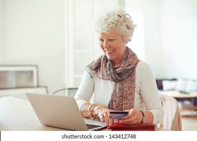 Happy old lady doing some shopping online using her laptop