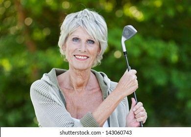 Happy old lady holding the golf stick standing in the golf club.