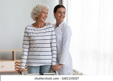 Happy old lady with walker stand hug female nurse or caregiver look in distance thinking dreaming of healthy future, smiling senior mature patient with walking frame and woman doctor feel hopeful