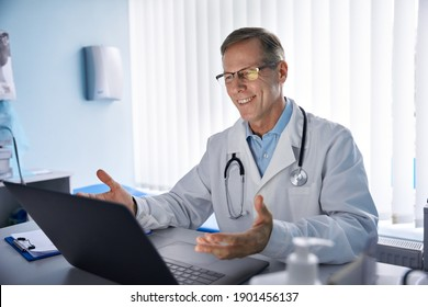 Happy old male doctor physician talking, consulting patient online by webcam video call on laptop computer. Telemedicine conference virtual tele meeting. E appointment, telehealth zoom therapy. - Shutterstock ID 1901456137
