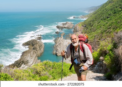 Happy old man just reaches the top of hill. Shot on the Otter trail in the Tsitsikamma National Park, Garden Route area, Western Cape, South Africa.