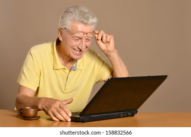 happy old man with laptop at the table