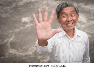 happy old man pointing up five fingers, smiling senior, positive retired pensioner portrait