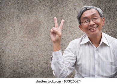 happy old man pointing up two finger, smiling senior, positive retired pensioner portrait