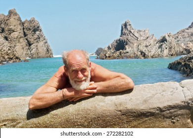 Happy old man rests on rocky beach. Shot on the Otter trail in the Tsitsikamma National Park, Garden Route area, Western Cape, South Africa.