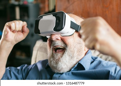 happy old man using virtual reality goggles at home