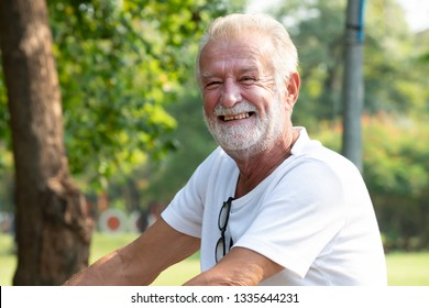 Happy old man with a white beard and a smile in the park.Cheerful portrait of elder man enjoying peaceful nature - Happy time senior man in the garden on summer season,Relaxation time Concept.